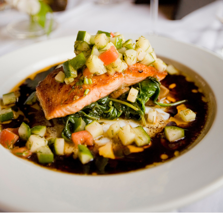 An image of salmon topped with vegetables